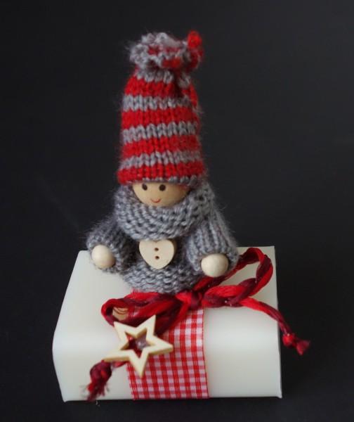 grauer Pulli, gestreifte Mütze, rotes Karoband